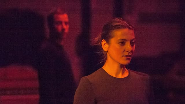 Eine Frau steht auf der Bühne. Hinter ihr steht ein Mann. Sie sind rot beleuchtet.