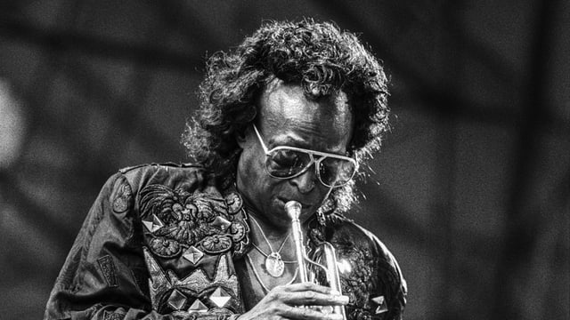 Eine Schwarzweiss-Aufnahme von Miles Davis, Trompete spielend