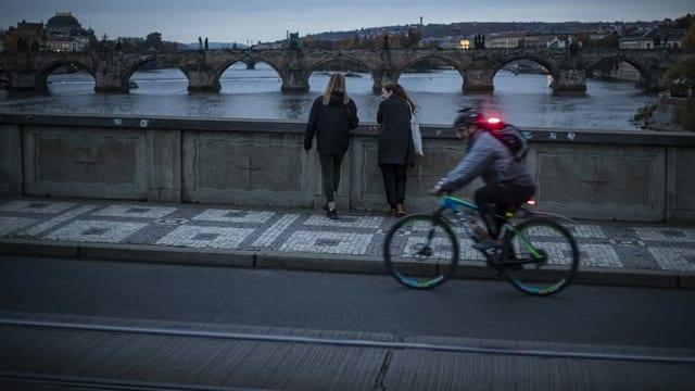 Zwei Frauen auf Brücke. Davor Velofahrer.