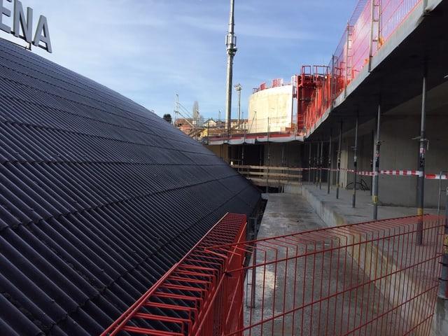 Rechts ein Betonbau, links ein Wellblechdach.
