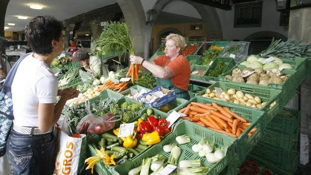 Eine Frau, die an einem Marktstand in Luzern Gemüse einkauft