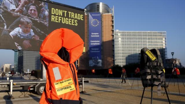Eine Schwimmweste steht vor einem Plakat mit der Aufschrift «don't trade refugees» in Brüssel.