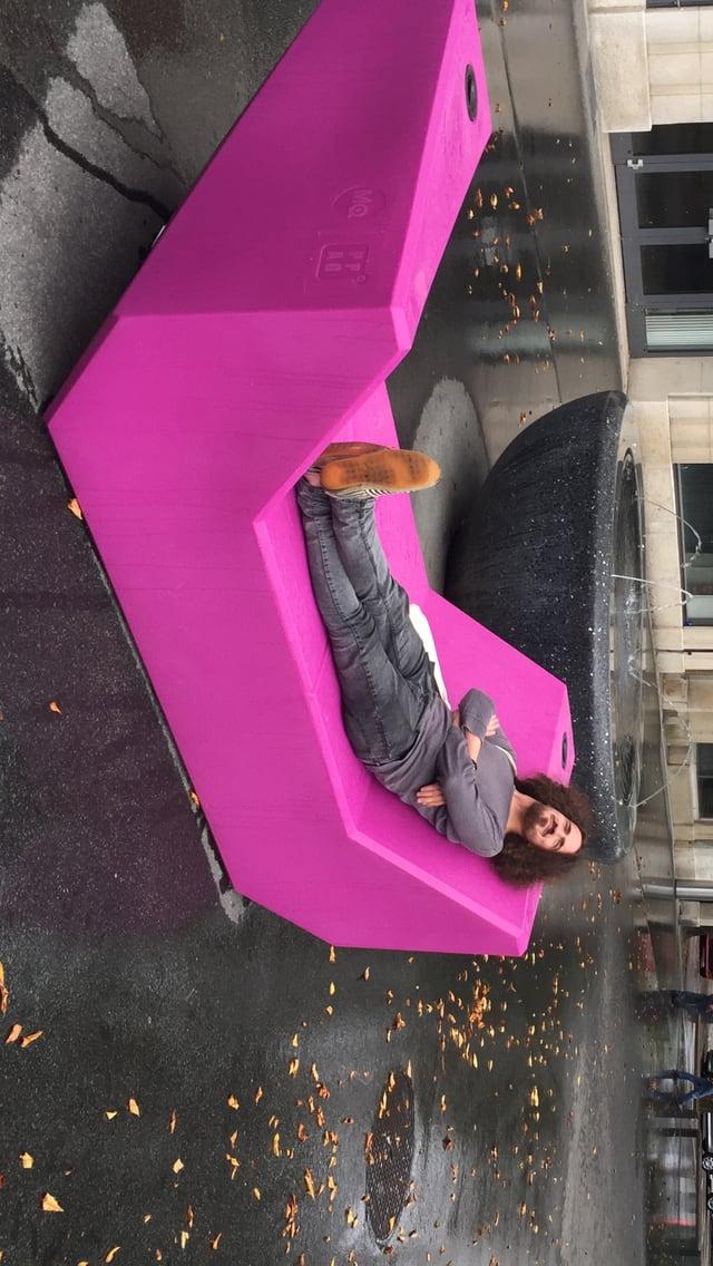 Ein Mann sitzt im Freien auf einem violetten Möbelstück aus Plastik
