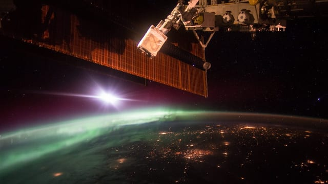 Eine Aufnahme der ISS, unter ihr die Erde bei Nacht, am Horizont geht die Sonne auf