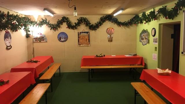 Ein Zivilschutzraum mit vier roten Tischen, bedeckt mit roten Tischtüchern. An der Wand Tannenzweige, geschmückt mit Christbaumkugeln.
