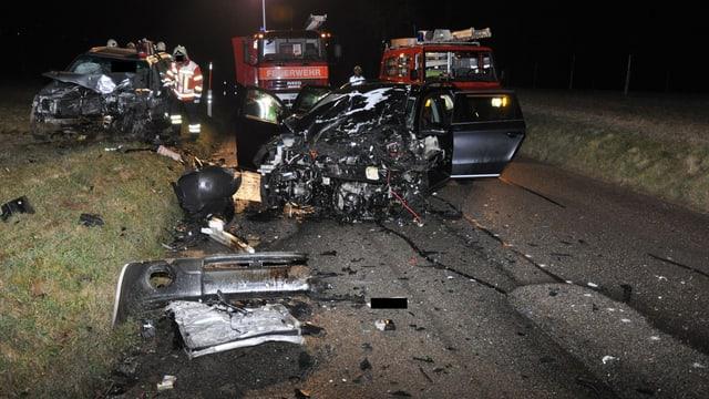 Zwei bis zur Unkenntlichkeit zerstörte Fahrzeug, im Hintergrund Feuerwehrautos