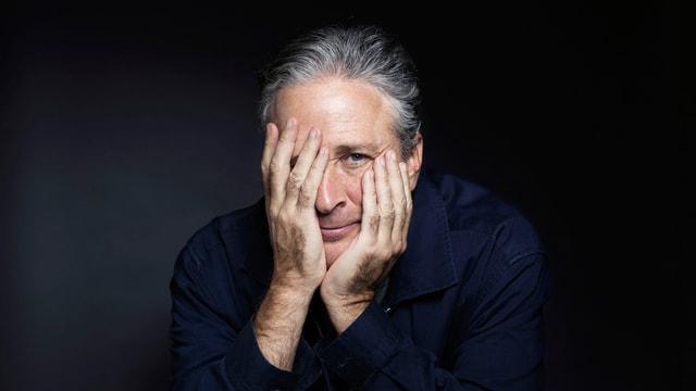 Ein Mann mit zurückgekämmten grauen Haaren, eine Hand leicht über dem Gesicht.