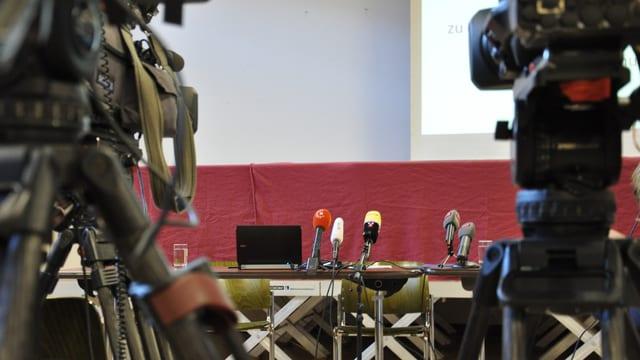 Ina maisa cun microfonas, e da la vart cameras da televisiun.