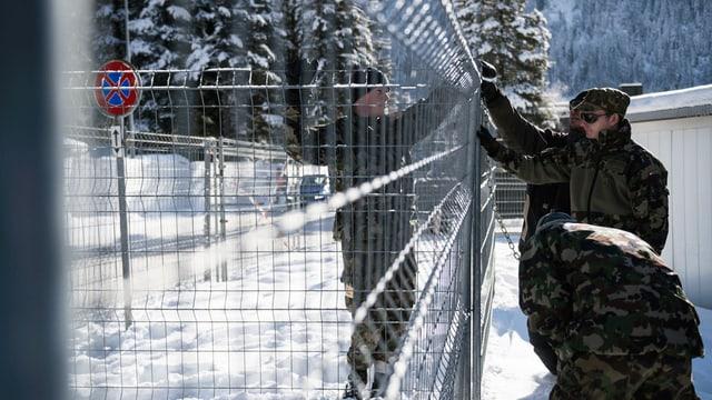 Soldaten vor Gitterzaun