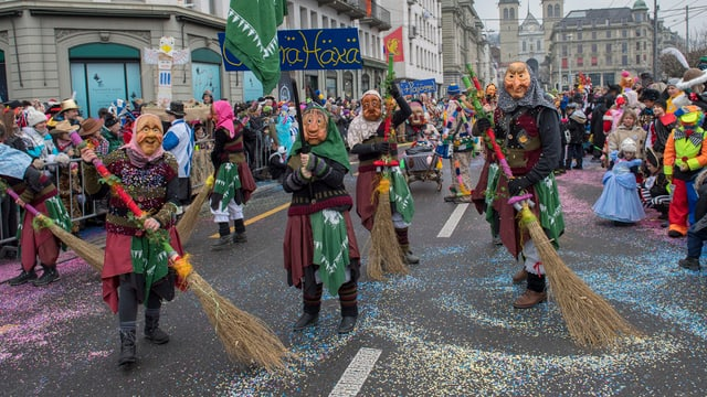 Fasnachtsumzug in Luzern mit Hexen die grosse Besen schwingen.