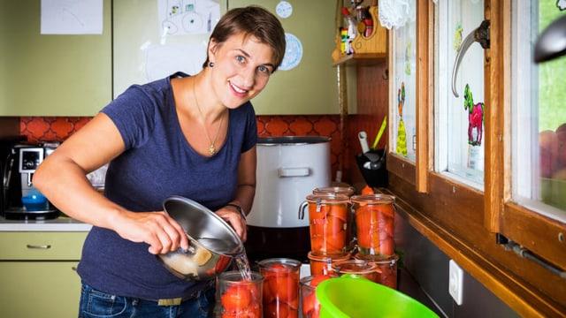 Manuela Barmettler füllt in ihrer Küche Tomaten in Einmachgläser.