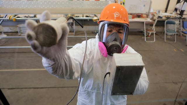 Ein Arbeiter im Schutzanzug misst die Strahlenwerte.