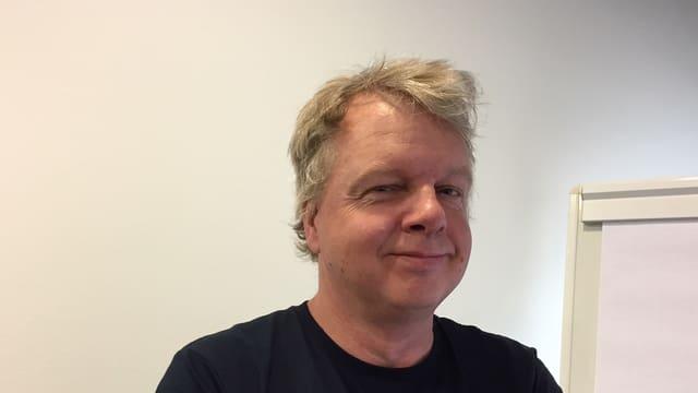 Ein Mann mit blonden Haaren steht vor einer weissen Wand und blickt in die Kamera.