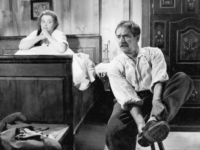 Filmszene mit einer Frau, die im Bett sitzt und einem Mann, der sich die Schuhe anzieht.