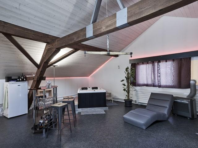 Ein Dachraum mit Trapezen, Liege, Bar und Kühlschrank.