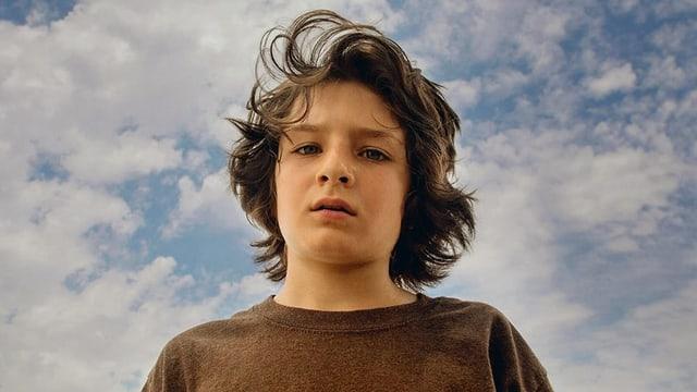 Junge blickt direkt in der Kamera, die ihn aus der Froschperspektive vor blauem Himmel ablichtet.