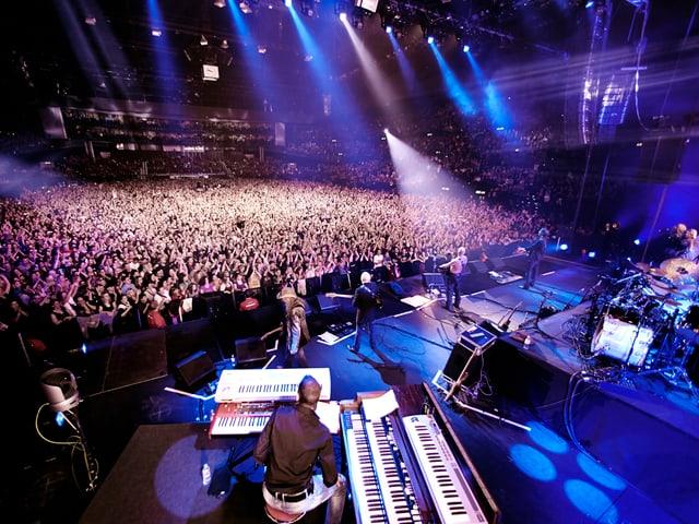 Mann, der auf einer Bühne einer grossen Halle steht.