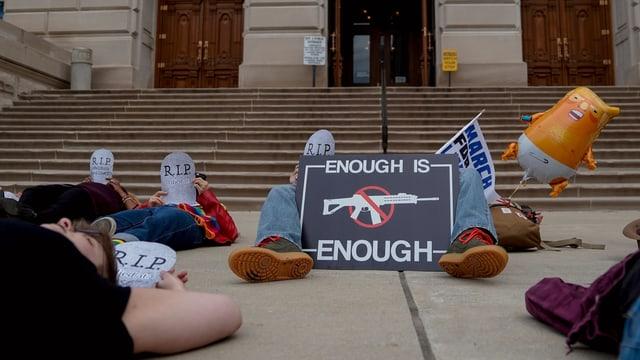 Menschen liegen auf dem Boden. Auf Plakaten steht Genug ist genug und R.I.P.. Sowie ein Verbotsschild mit einer durchgestrichenen Waffe.