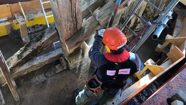 Zimmermann sägt alte Holzbalken heraus.