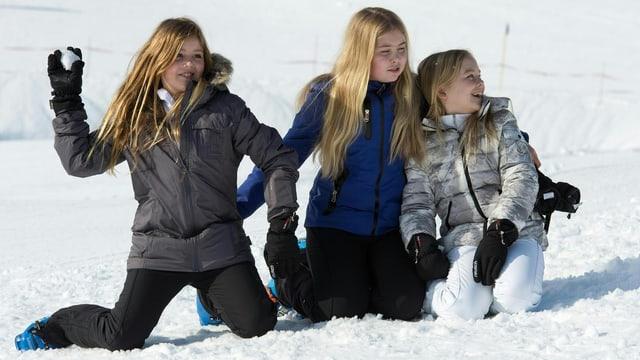 Drei Mädchen mit blonden Haaren knien im Schnee und liefern sich eine Schneeballschlacht.