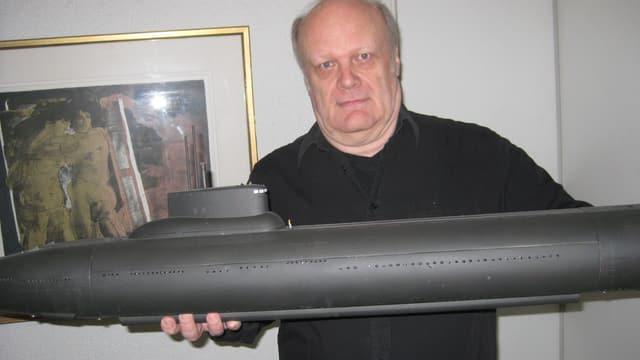 Ein Mann mit einem Modell eines Unterseebootes.
