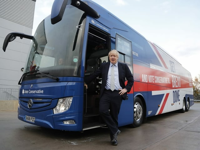 """Johnson lehnt an einem Bus mit der Aufschrift """"Get Brexit Done""""."""
