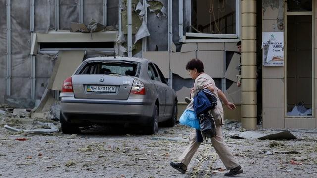 Eine Frau läuft neben einem zerstörten Haus vorbei