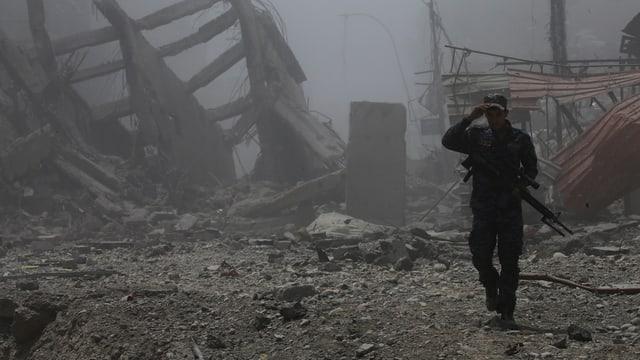 Ein Mann mit Gewehr in Ruinen.