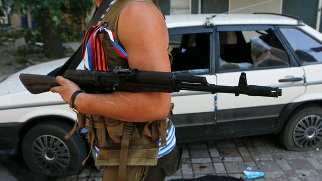 Pro-russischer Rebell läuft an einem zerstörtem Auto vorbei