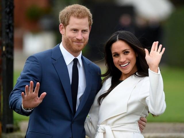 Prinz Harry und Meghan Markle winken den Fotografen zu.