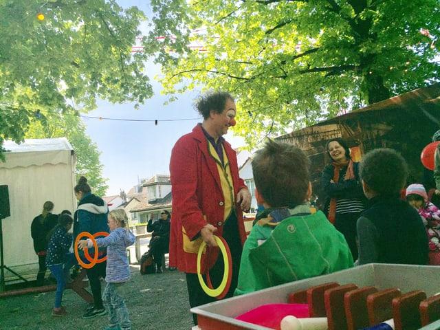 Ein Mann in roter Clownsjacke, davor viele Kinder