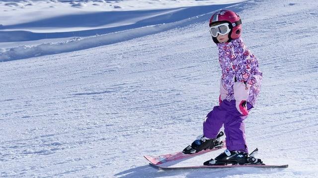 Kind mit Ski auf der Piste
