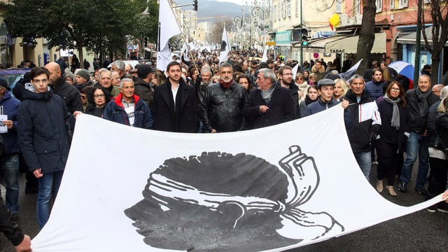 Demonstranten tragen riesiges Tuch mit Korsenkopf.
