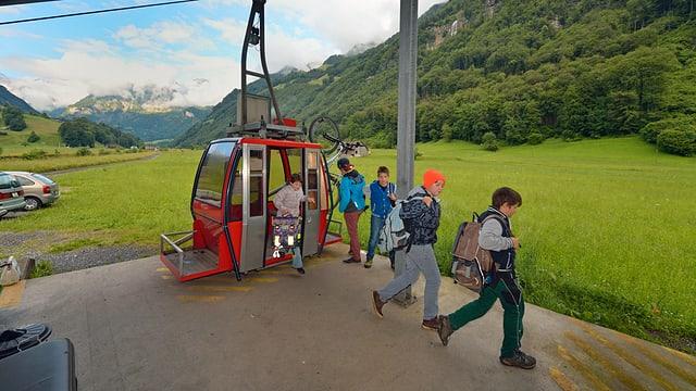 Schülerinnen und Schüler steigen aus einer roten Seilbahnkabine aus.