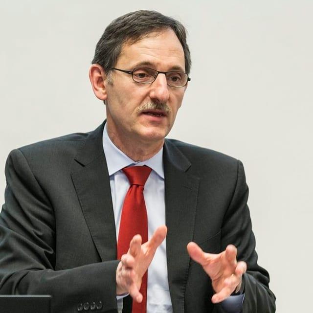 Regierungsrat Mario Fehr, kurze Haare, Brille, Schnauz, in blauem Hemd und roter Krawatte.