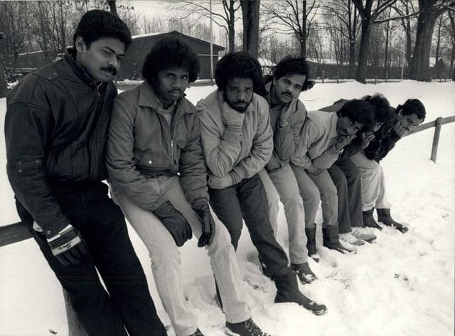 Schwarz-Weiss-Aufnahme: Tamilische Männer lehnen sich gegen an einen Zaun.