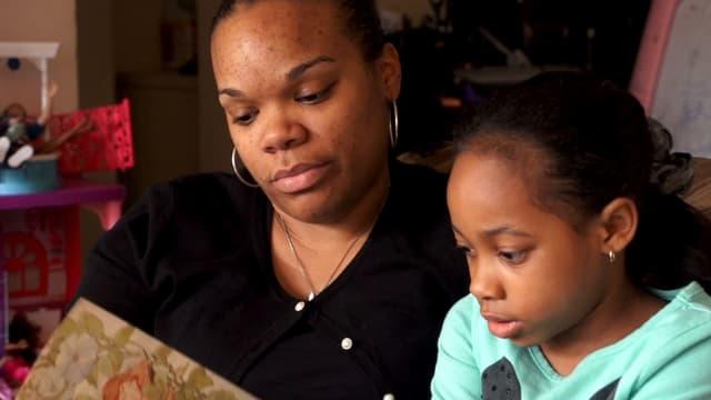 Eine Mutter liest ein Buch mit ihrer Tochter.