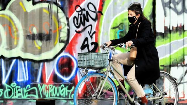 Eine Frau auf dem Velo mit einer Maske.