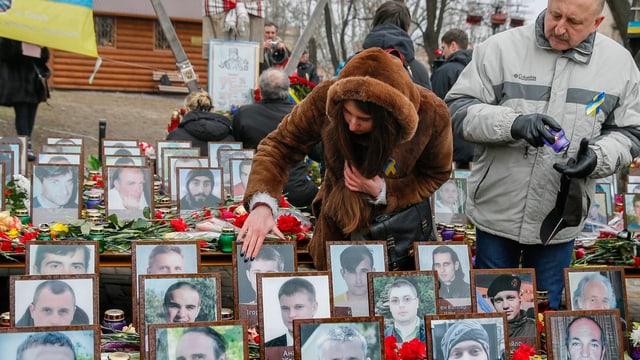 Eine Frau und ein Mann betrachten Fotos von getöteten Demonstranten.