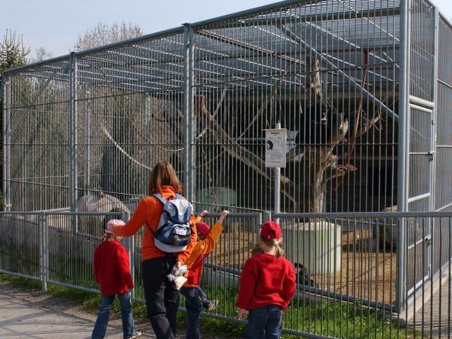 Eine Frau und drei Kinder stehen vor einem Käfig.