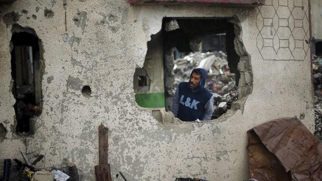 Ein Mann schaut durch ein Loch in einem zerbombte Haus.