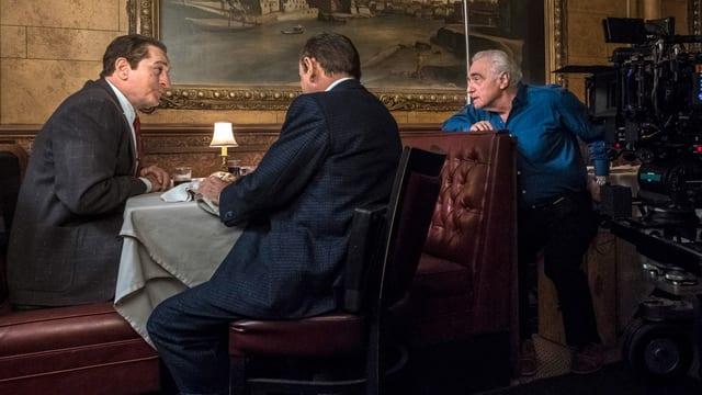 Zwei Männer im anzug an einem Tisch in einem noblen Restaurant. Vom Nebentisch sitz neben einer Kamera der regisseur und spricht mit den beiden.