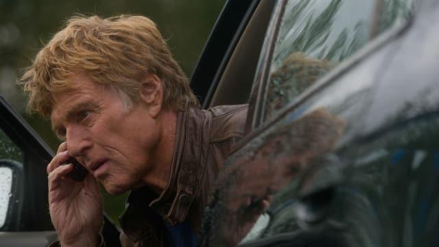 Ein Mann steigt telefonierend aus einem Auto.