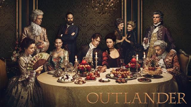 Die Hauptdarsteller der Serie «Outlander» sitzen und stehen um einen reichgedeckten Esstisch