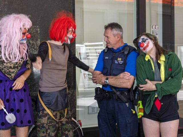 Demonstranten in Clown-Kostümen und ein Polizist