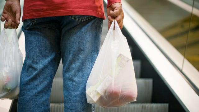 Mann auf Rolltreppe mit Plastiktüten