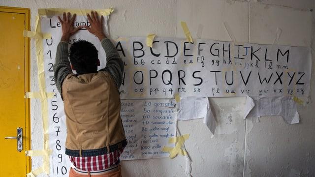 Ein Mann klebt behelfsmässig Zettel mit dem ABC an die Wand, links eine gelbe Tür.