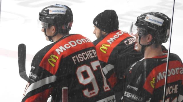 Trais giugaders da hockey a la banda