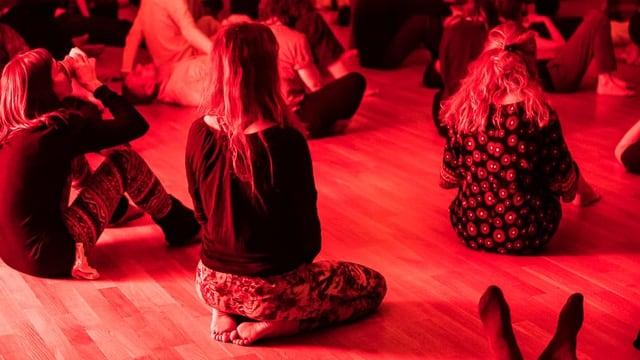 Menschen sitzen am Boden in einem rot beleuchteten Raum