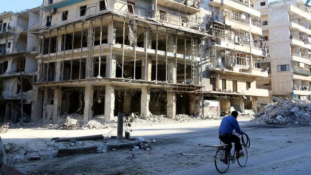 Zerstörter Strassenzug in Aleppo, Velofahrer auf Strasse